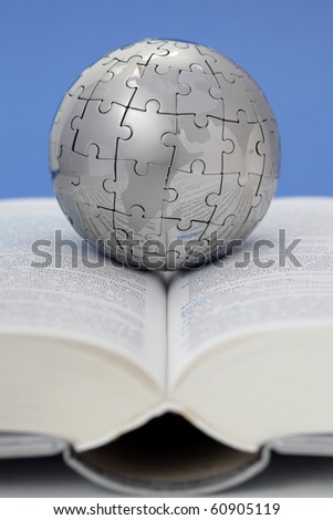 Metal puzzle globe on open book - stock photo