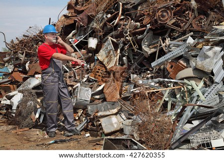 Metal recycling, worker speaking by mobile phone and pointing to heap of scrap metal