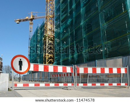 Metal red and white striped barriers with no access sign restricting access to construction site by unauthorized persons - stock photo