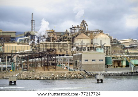 Metal refinery on bank of river. Heavy industry. - stock photo