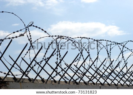 metal rods and wound barbed wire on fence - stock photo