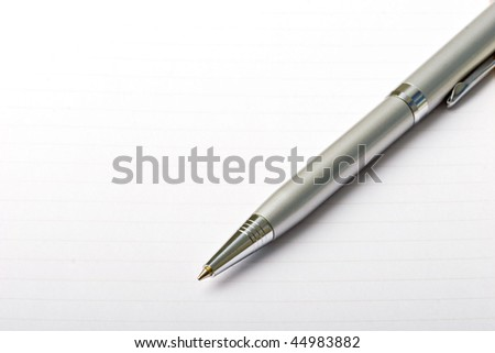 Metal roller pen on a note pad paper sheet close up