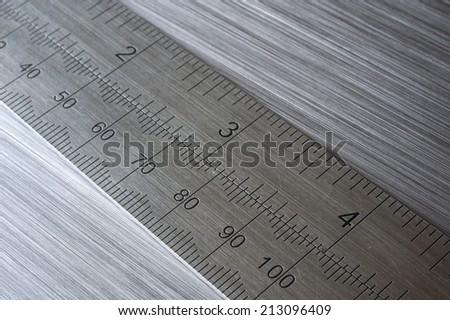 metal ruler on brushed metal background - stock photo