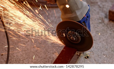 Metal sawing with hand grinder. Sparks while grinding iron.