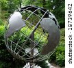 metal sculptured globe of the planet earth in a wooded area - stock photo