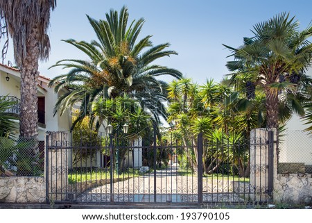 Metal security gate protecting a house and gardens - stock photo
