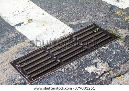 metal sewer grate for drainage system on asphalt road - stock photo