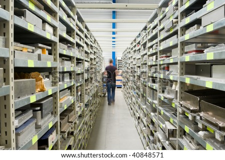 Metal Shelves With Spare Parts And Technician In Plant Interior