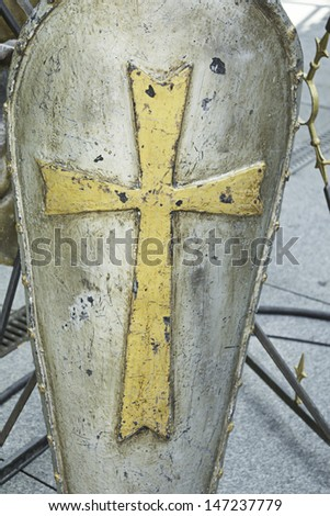 Metal shield with golden cross in medieval festival, recreation - stock photo
