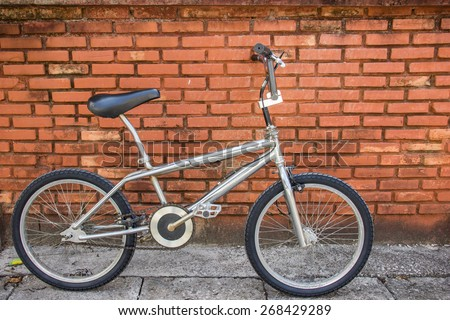 metal shine bicycle lean to the old brick wall - stock photo