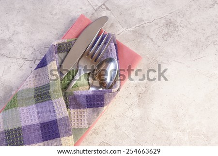 Metal silverware setting wrapped in cloth napkin, sitting on a complimentary colored cloth napkin and laying on a white marble surface with plenty of copyspace. - stock photo