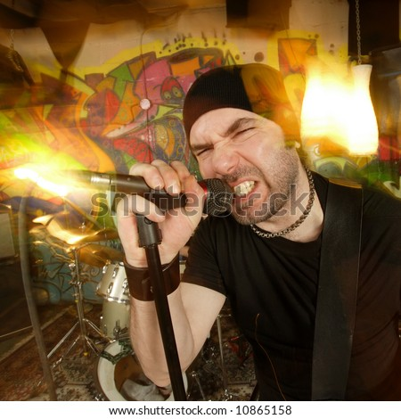 Metal singer cussing into the microphone.  Shot with strobes and slow shutter speed to create lighting atmosphere and blur effects. - stock photo