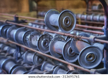Metal Spools Sitting on a Loom in the Abandoned Lonaconing Silk Mill in Lonaconing, Maryland - stock photo