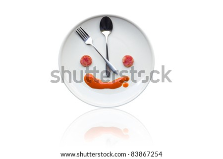 Metal spoon and fork arrange as clock face on white dish with artistic human like face from food