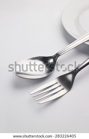 Metal spoon and fork on white background