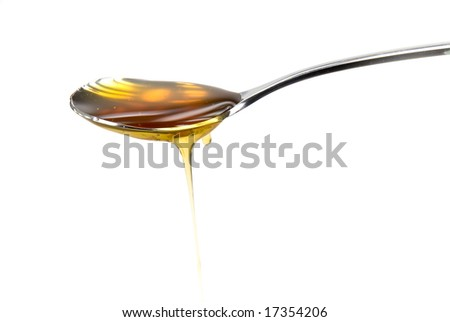 Metal spoon filled with honey over a white background