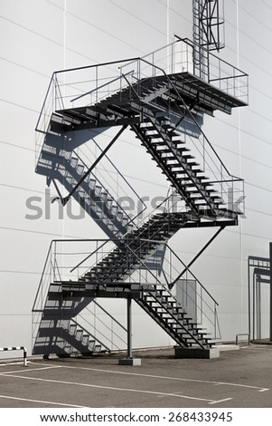 Metal staircase on fire exit at big factory - stock photo
