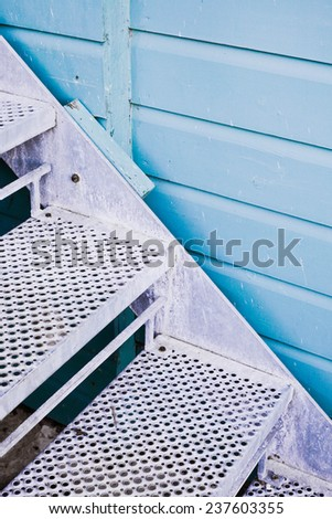 Metal stairs against a blue wooden wall - stock photo