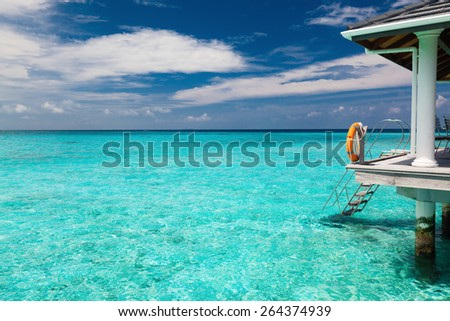 Metal stairs from wodden jetty leading into shallow tropical sea - stock photo