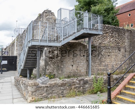 metal stairs next to an ancient wall