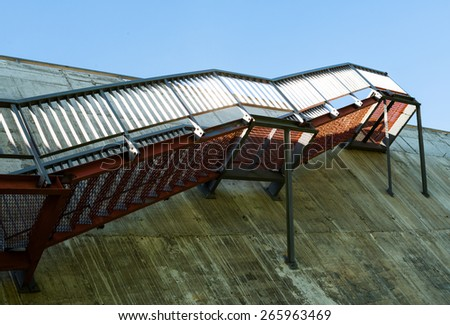 Metal stairs on the gray concrete wall. - stock photo