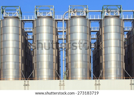 metal steel tank storage in heavy industry estate plant against clear blue sky use for industrial and factory manufacting of oil fuel and fossil energy background,backdrop - stock photo