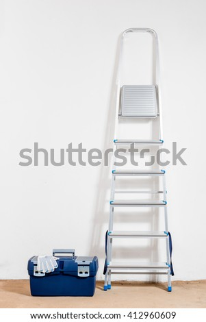 metal stepladder and a tool box in the room - stock photo