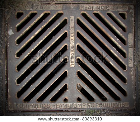 metal storm drain with warnings - stock photo