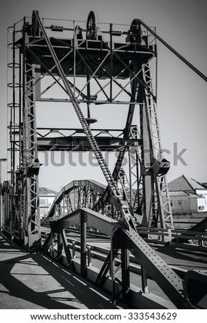 Metal structure elevation bridge over Sado river. Alcacer do Sal, Portugal. BW filtered shot - stock photo