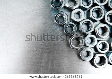 Metal style. Fixing elements. Nuts on scratched metal background. - stock photo