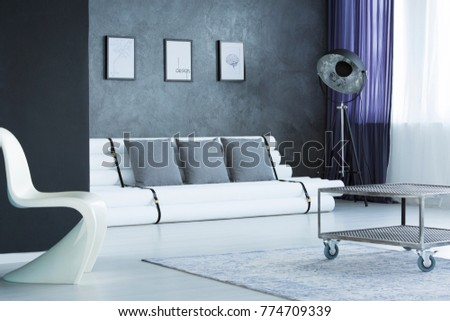 Metal table on grey carpet and modern white chair in living room with designer lamp next to sofa