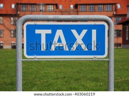 Metal Taxi Sign Isolated Closeup with Building and Grass Background - stock photo