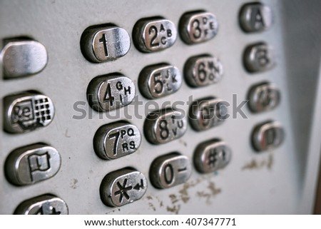 Metal telephone dial in the public phone booth with black letters and numbers on the silver plated  buttons