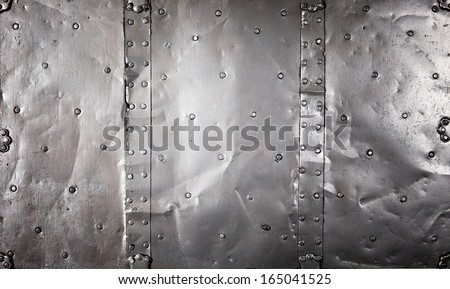 Metal texture of old metal plates with scattered studs joined by riveted seams - stock photo