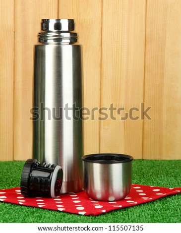 metal thermos on grass on wooden background - stock photo