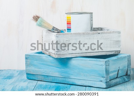 Metal tin can with paint and brush in wooden box - stock photo