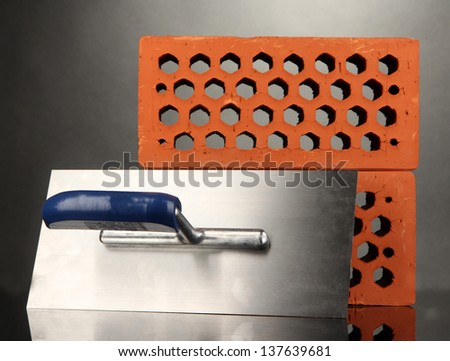 Metal tool for building and bricks isolated on black - stock photo