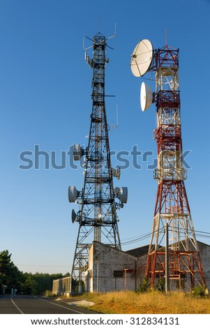 Metal tower or turret telecommunications satellite dishes reception and emission, side road  - stock photo