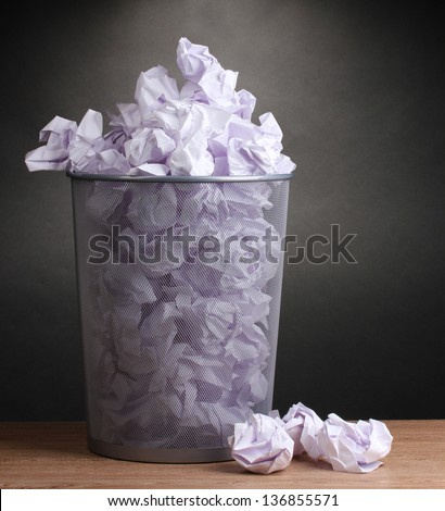 Metal trash bin from paper on wooden floor on gray background - stock photo