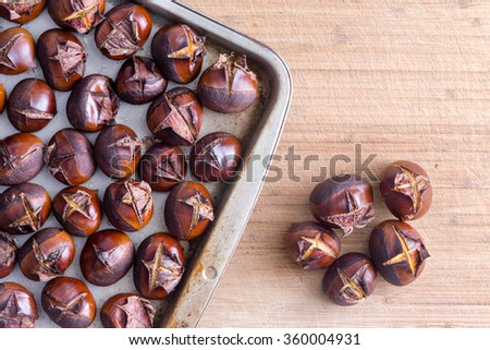 Metal tray of roasted chestnuts on wooden table next to five separate nuts - stock photo