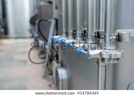 metal tubes on stainless tanks with wine - stock photo