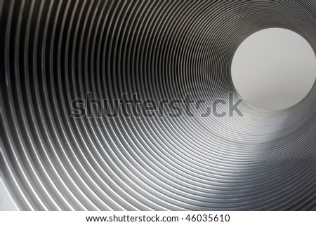 Metal tunnel of metal tube showing light at end of tunnel. - stock photo
