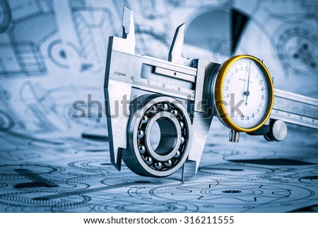 Metal vernier caliper and Ball bearings on technical drawing a blue toning - stock photo