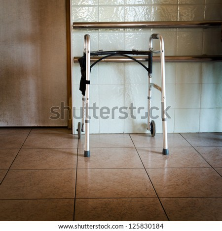 Metal walker parked in hospital hallway.