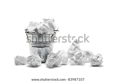 Metal waste basket filled with crumpled paper - waste or frustration concept - stock photo