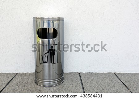 metal waste bin against a wall