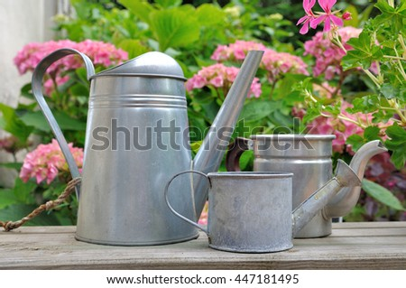 metal watering cans on table in front of pink flowers - stock photo
