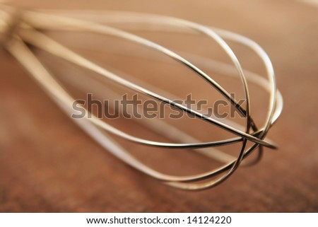 Metal whisk on wooden surface - stock photo