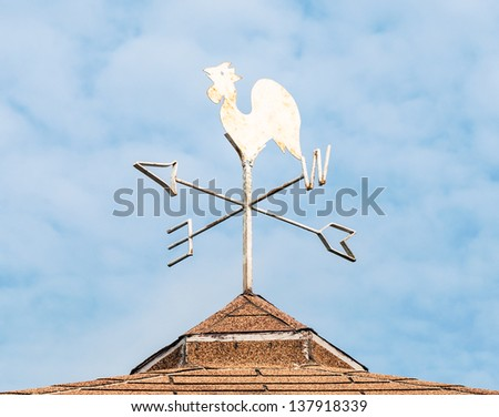 Metal wind direction tool on the top of farmer house. - stock photo