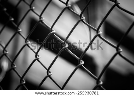 Metal wire fence or cage with blur background in black and white - stock photo